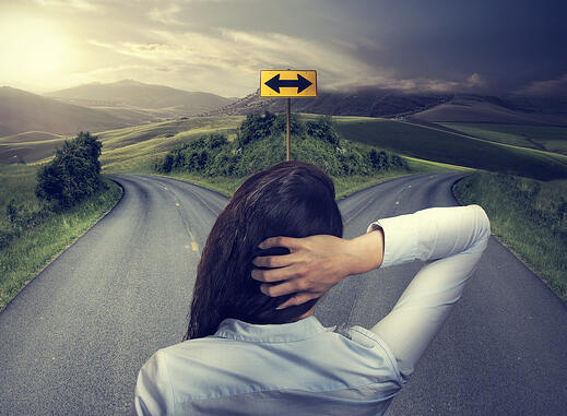 business woman in front of two roads thinking deciding hoping for best taking chance